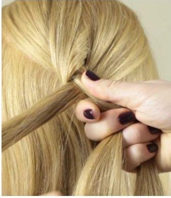Девушка зажимает пальцами пряди при плетении обратной французской косы