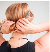 Девушка убирает концы внутрь греческой причёски