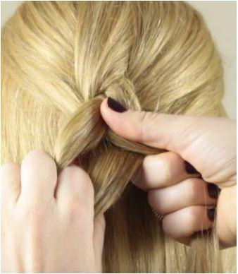 Девушка сжимает плетение обратной французской косы