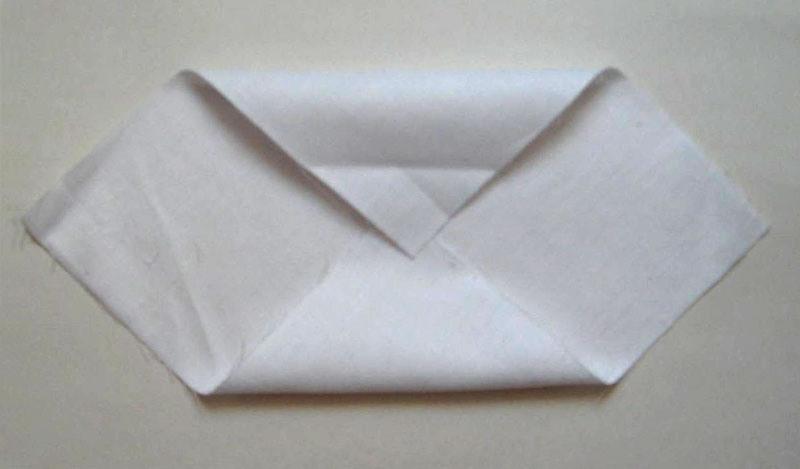 Белая ткань, сложенная углами к центру