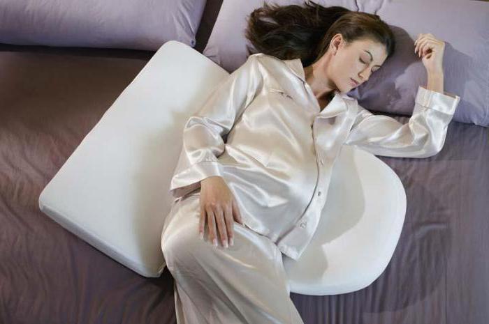 Беременная женщина спит на кровати