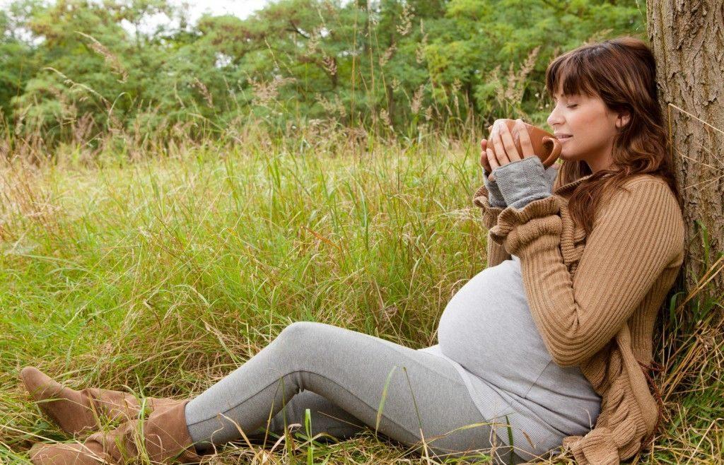 Беременная женщина пьёт чай на природе