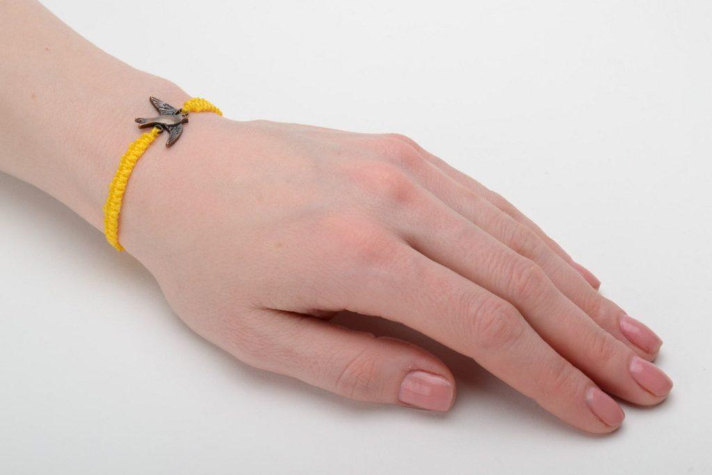 Браслет-нить жёлтого цвета на руке