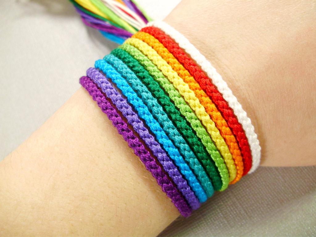 Браслеты-нити разных цветов на руке