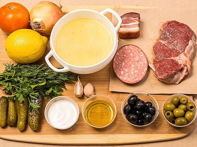 Бульон, мясные продукты и овощи для солянки