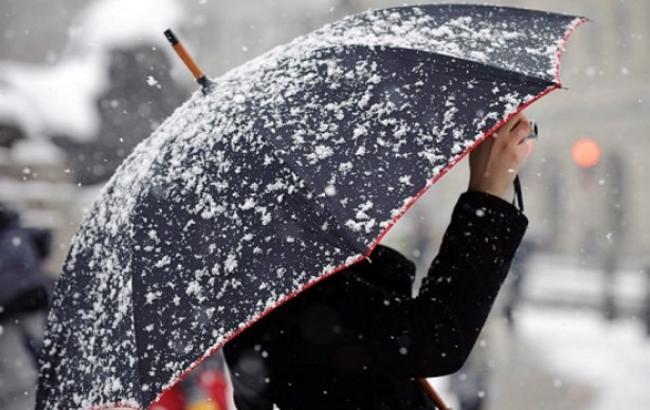 Человек прячется под зонтом от снега с дождём