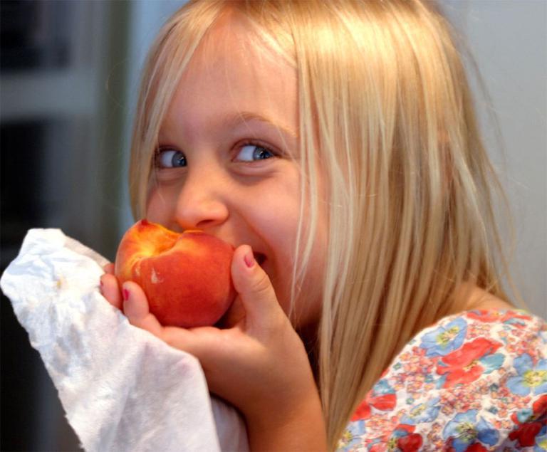 Девочка ест абрикос