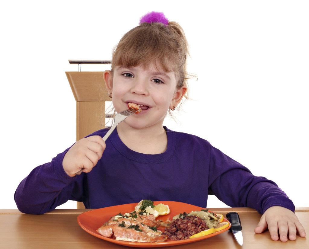 Девочка ест блюдо из печени