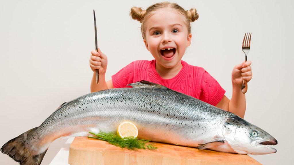 Девочка готовится съесть большую рыбу