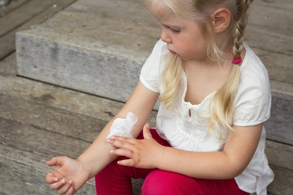 Девочка мажет руку кремом