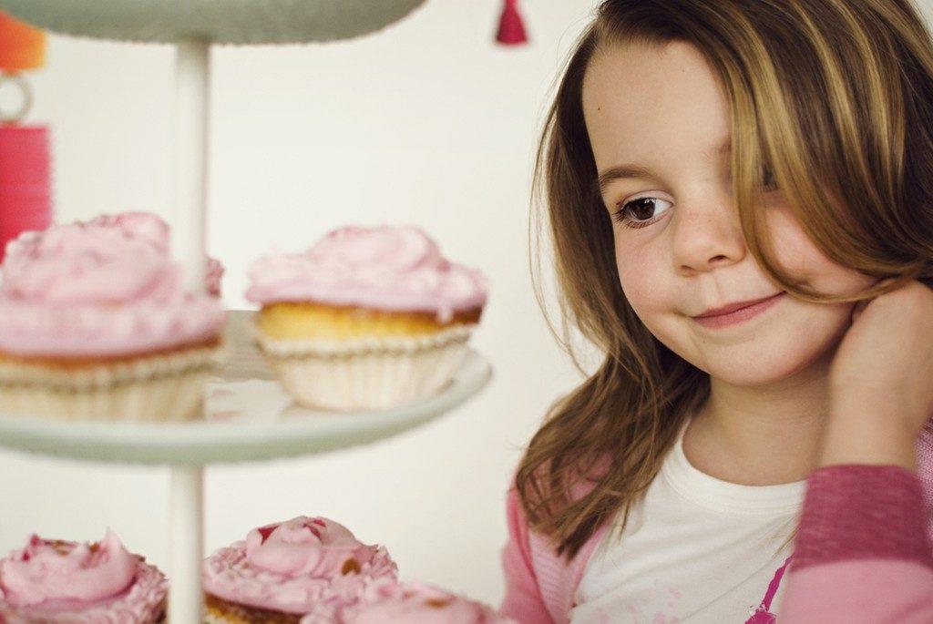 Девочка смотрит на кексы