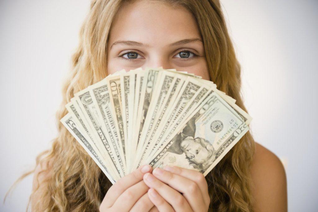 Девушка держит деньги веером