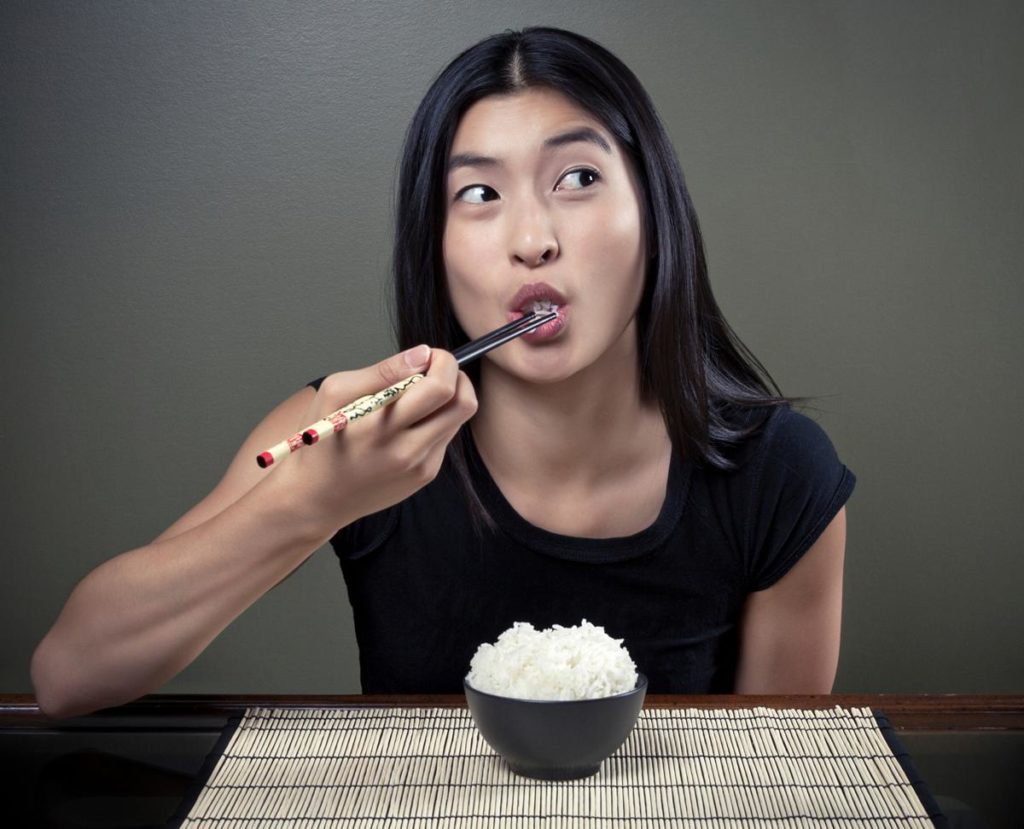 Девушка ест рис палочками