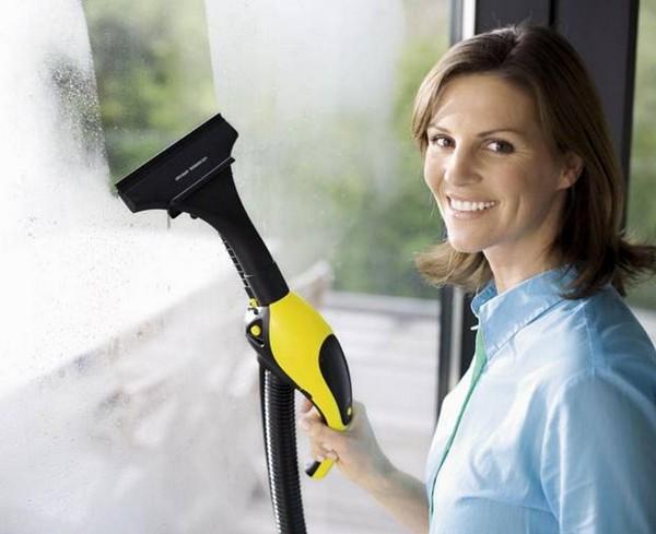 Девушка, моющая окно пароочистителем