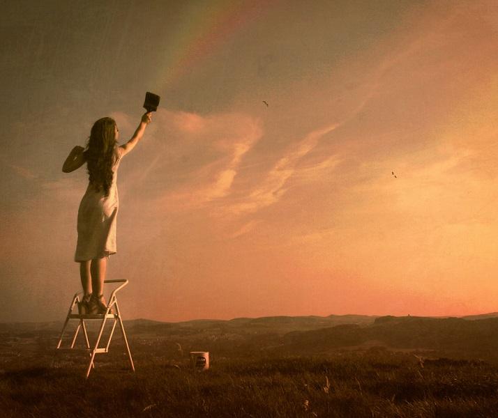 Девушка рисует радугу на небе