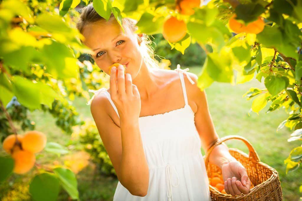 Девушка с корзинкой под абрикосовым деревом
