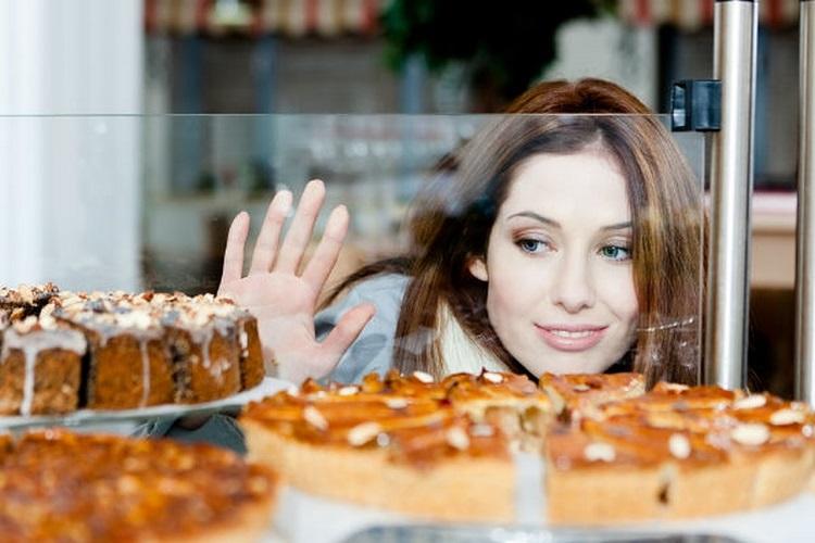 Девушка с удовольствием смотрит на сладкие пироги в витрине