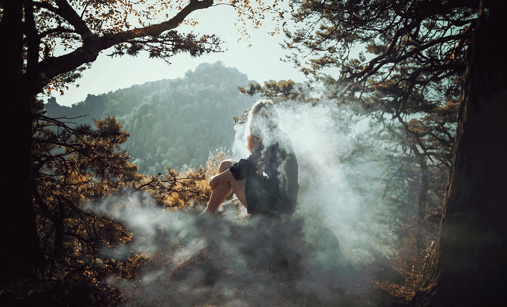 Девушка сидит в клубах дыма