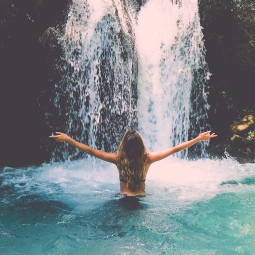 Девушка стоит в воде перед водопадом