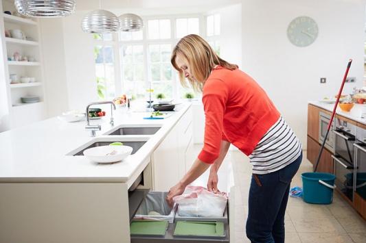 Девушка в красной кофте чистит кухонные шкафы