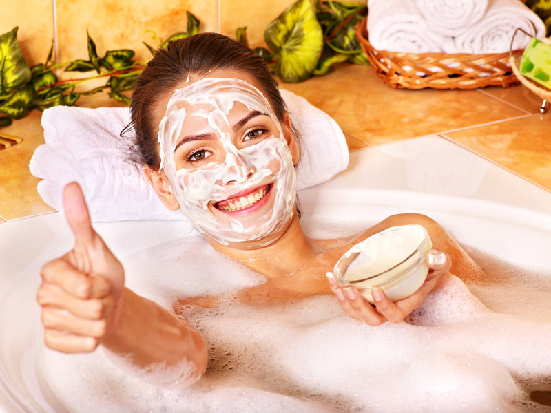 Девушка в ванной с маской из сметаны на лице