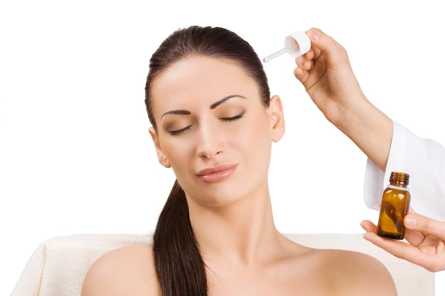Девушке наносят персиковое масло на волосы с помощью пипетки
