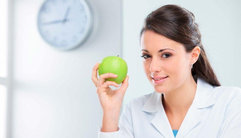 Врач-диетолог держит яблоко в руке
