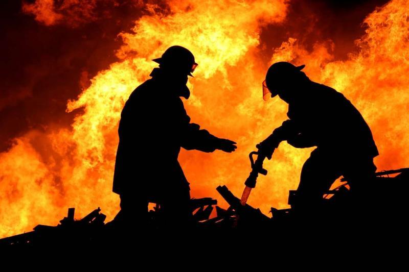 Двое пожарных тушат пожар