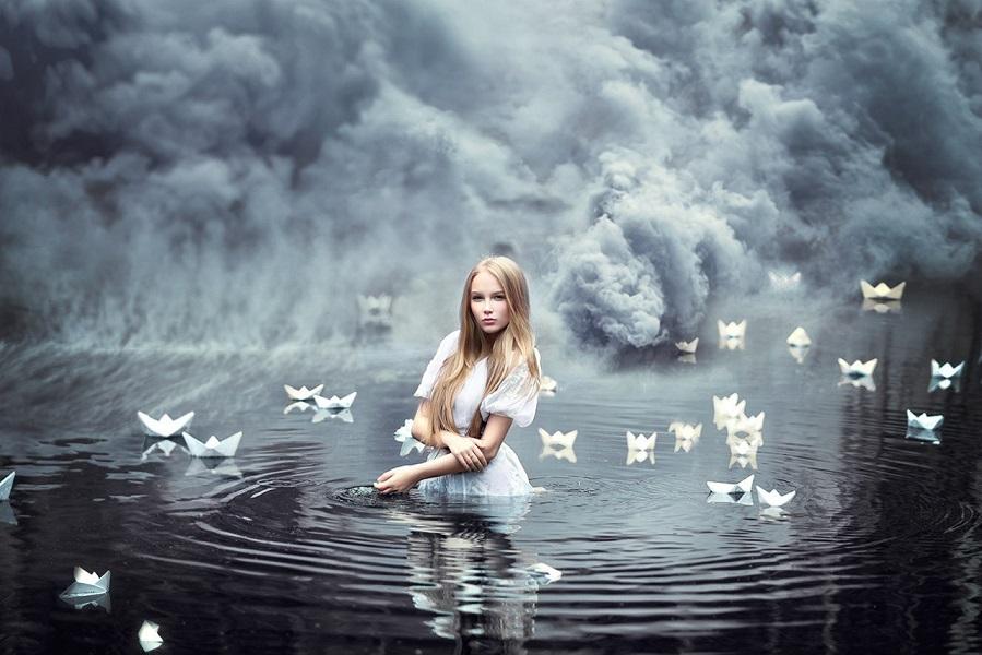 Девушка стоит в воде на фоне дыма