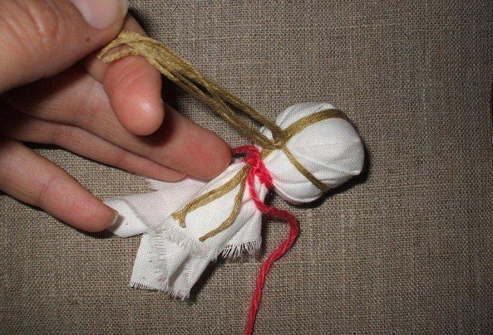 Нити в форме креста на голове куклы
