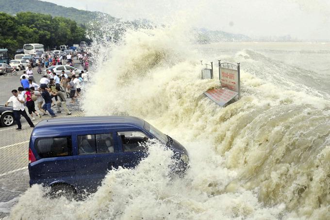 Гигантская волна сбивает с ног людей и смывает автомобиль