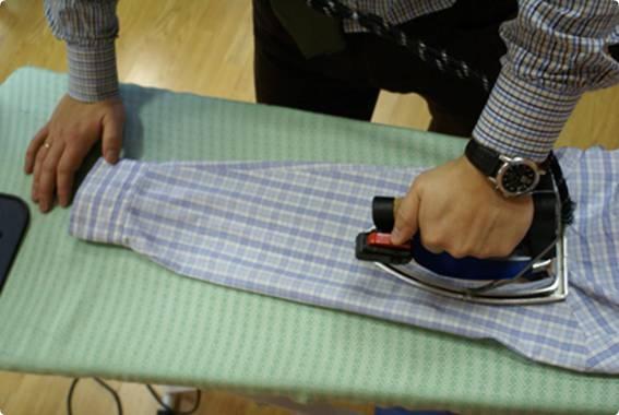 Рукав рубашки в голубую клетку на гладильной доске