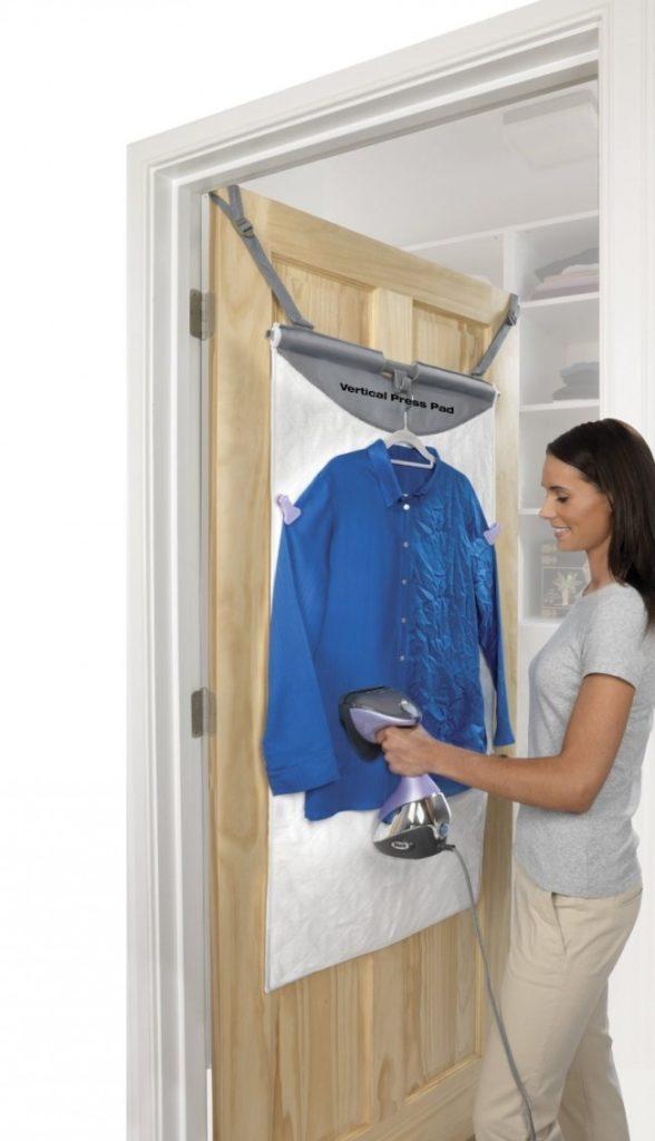 Женщина гладит рубашку вертикальным отпаривателем