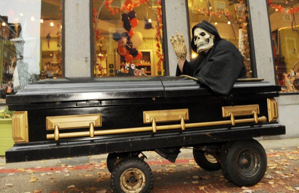 Гроб на колёсах с человеком в маске покойника внутри