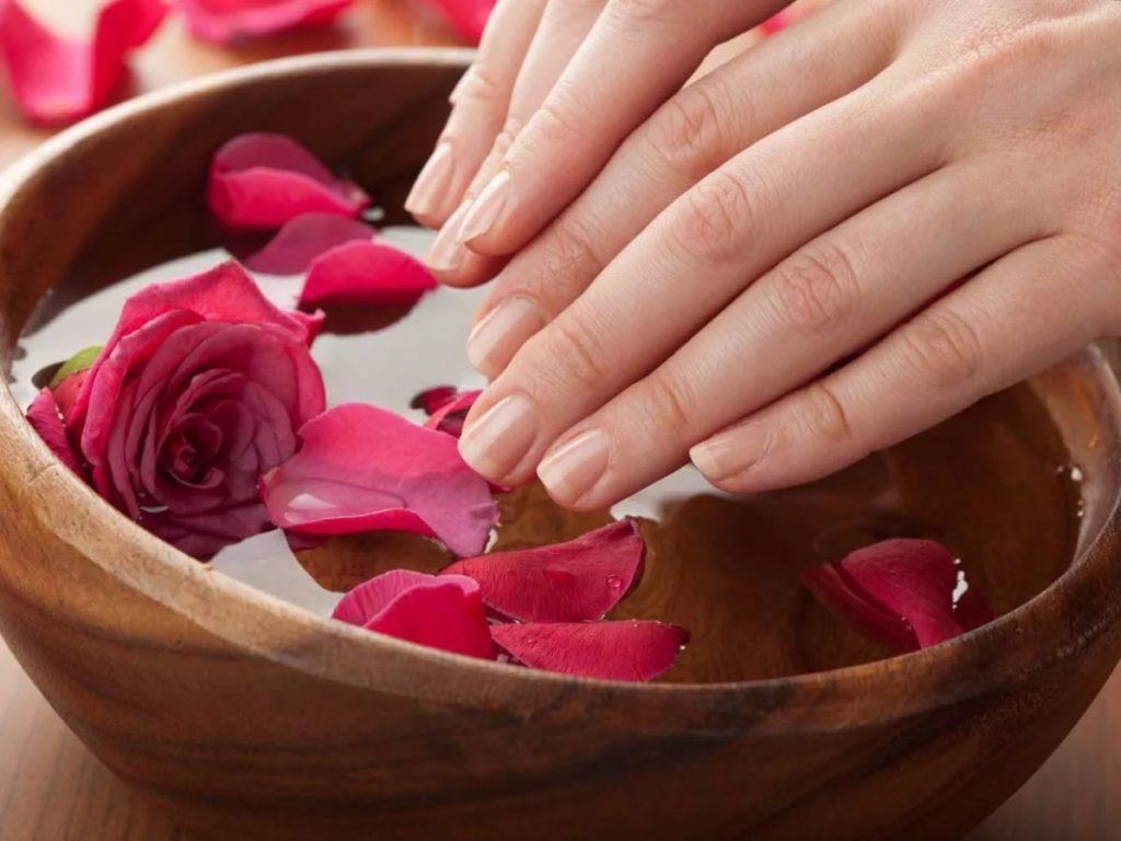 Кисти рук опускают в деревянную миску с водой и лепестками роз