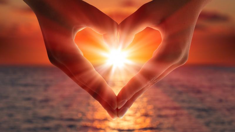 Ладони в форме сердца на фоне солнца