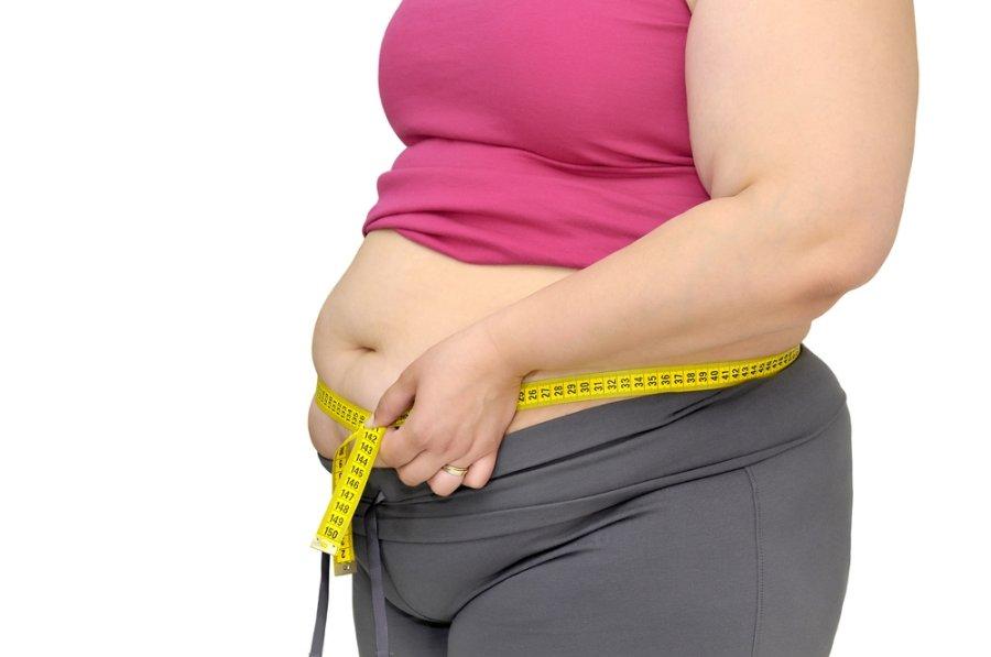 Полная женщина измеряет талию сантиметровой лентой