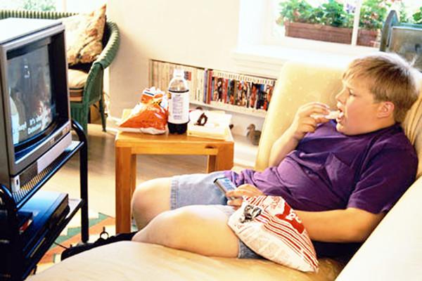 Мальчик ест перед телевизором
