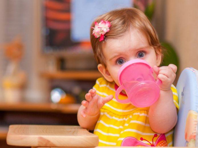 Девочка пьёт из своей кружки