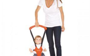 Мама держит малыша в вожжах-ходунках