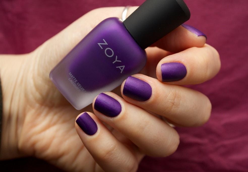 Матовый фиолетовый лак в руке