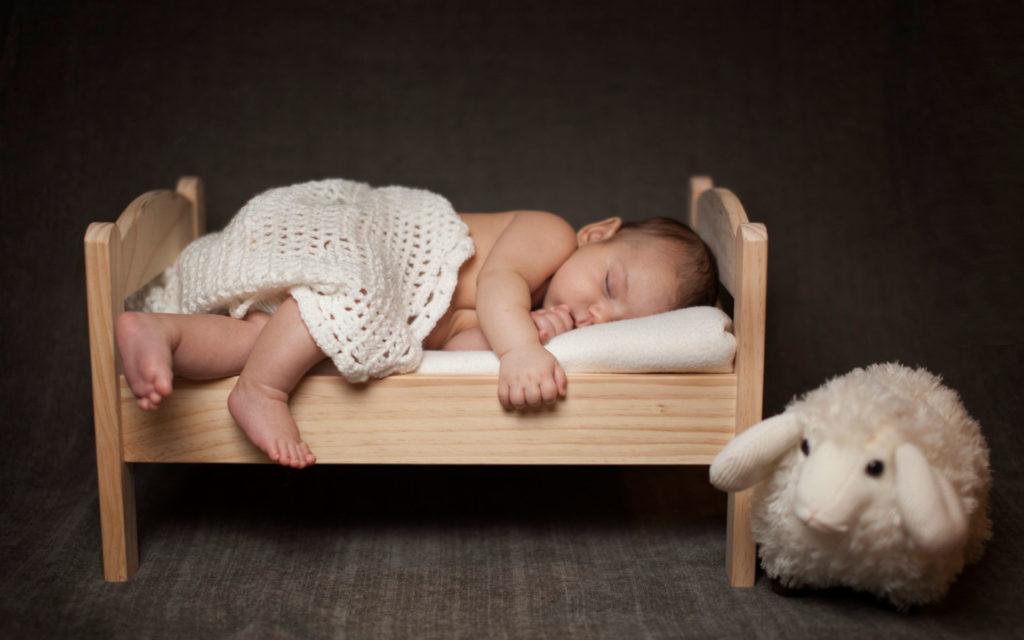 Младенец спит в кровати