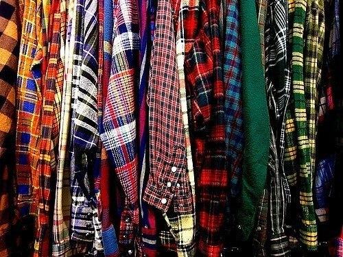 Много цветных рубашек на плечиках в шкафу