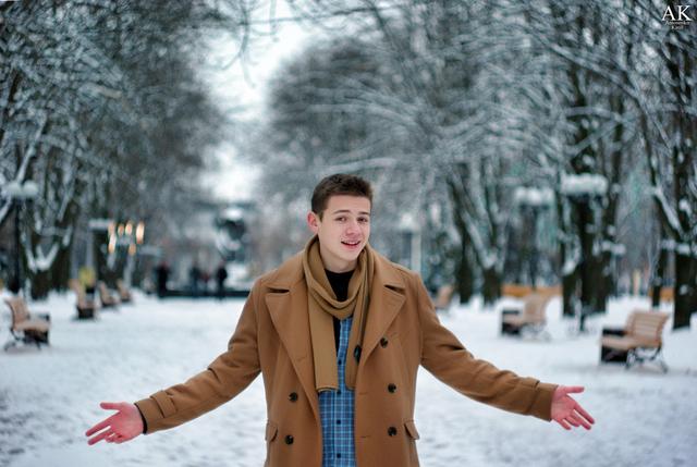 Молодой человек в заснеженном парке