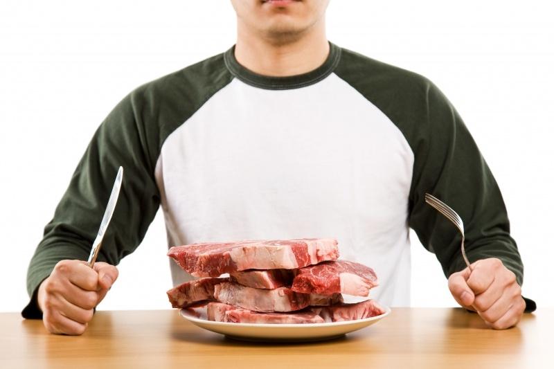 Мужчина ест сырое мясо