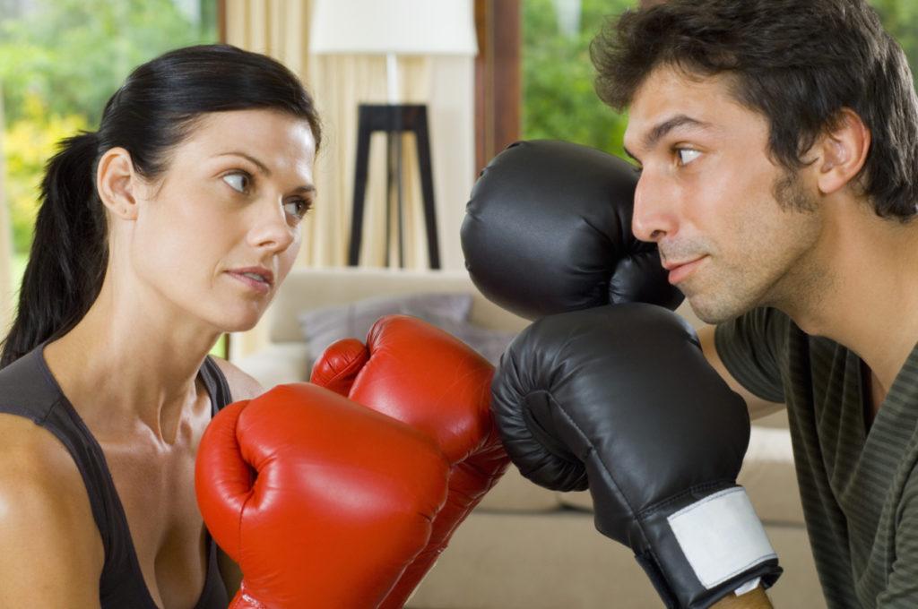 Мужчина и женщина в боксёрских перчатках смотрят друг на друга