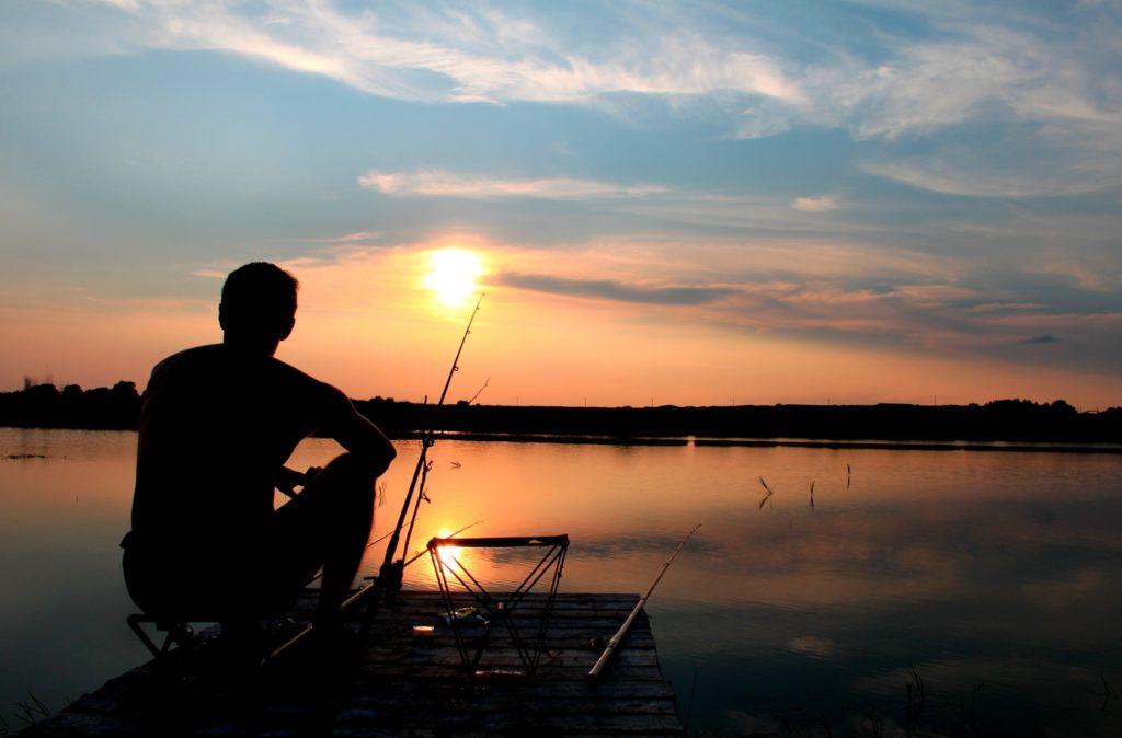Мужчина ловит рыбу в реке