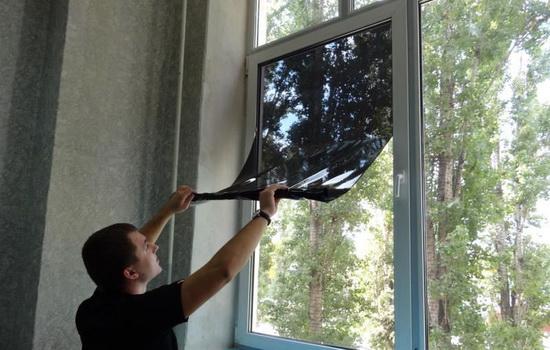 Мужчина, накладывающий на окно тонированную плёнку
