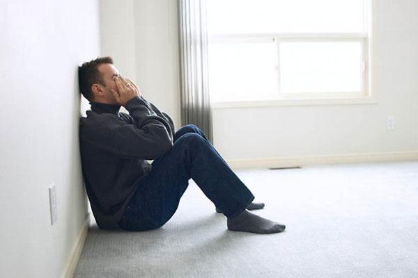 Мужчина плачет у стены