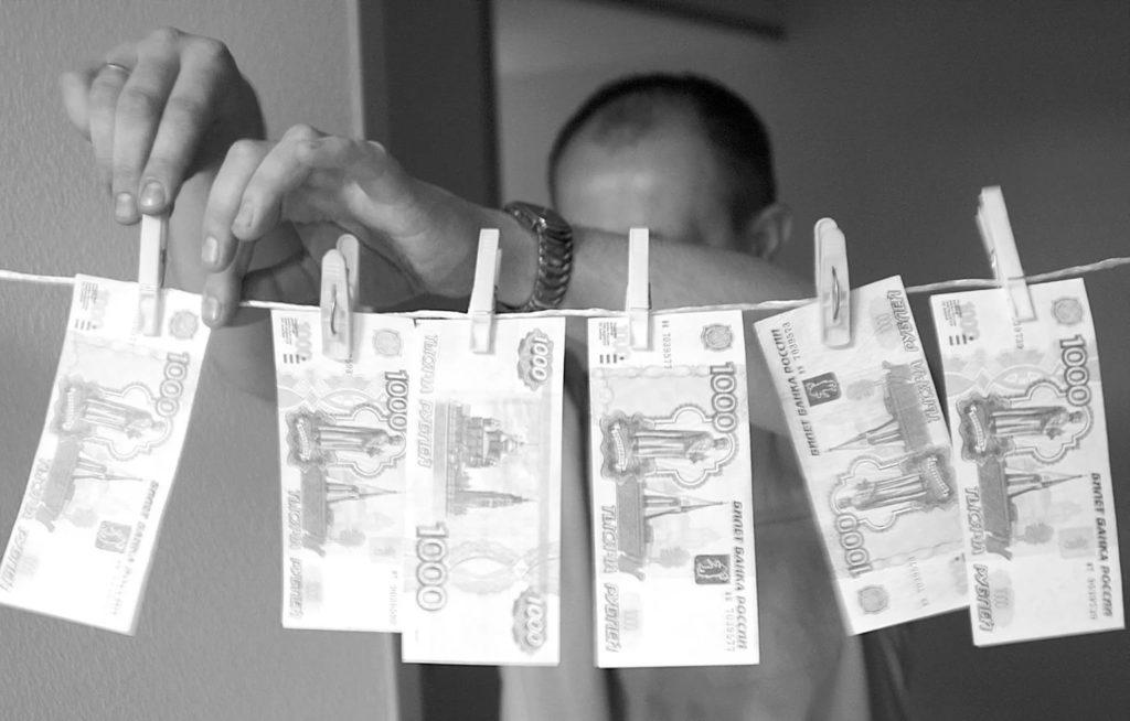 Мужчина развешивает деньги на верёвке